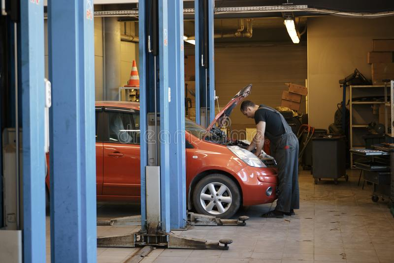 Specialist auto mechanic in the car service, checks the car, engine, engine, carburetor. Concept: repair of machines stock photos