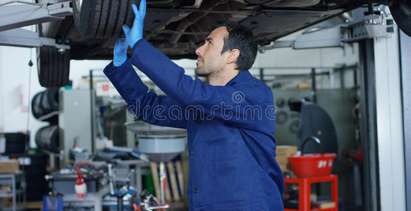 Specialist auto mechanic in the car service, repairs the car, makes transmission and wheels. Concept: repair of machines, fault di stock photography