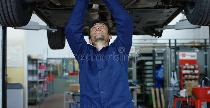 Specialist auto mechanic in the car service, repairs the car, makes transmission and wheels. Concept: repair of machines, fault di. Agnosis, repair specialist stock photo
