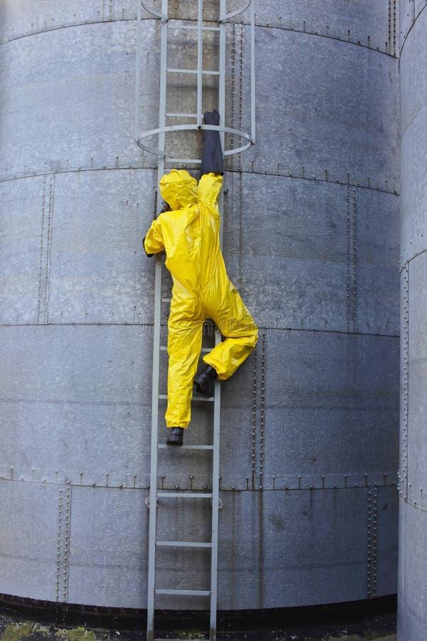 Specialist in beschermende eenvormig uitgaand een metaalladder op opslagtank stock afbeeldingen