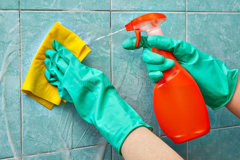 Yellow viscose napkin cleans foam cleaner from tiles in bathroom. Specialist from the cleaning service in green protective rubber gloves washes the tile in the royalty free stock photo