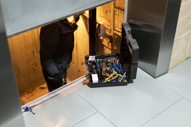 Specialist fixing or adjusting lift mechanism in elevator schaft. Regular repair, service and maintenance of elevator stock photo