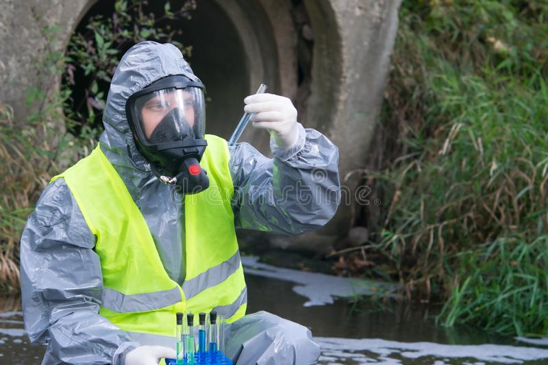 Specialist in a gray protective suit and mask, on the pond, takes a sample of liquid in tubes, close-up, there is a place for the royalty free stock image