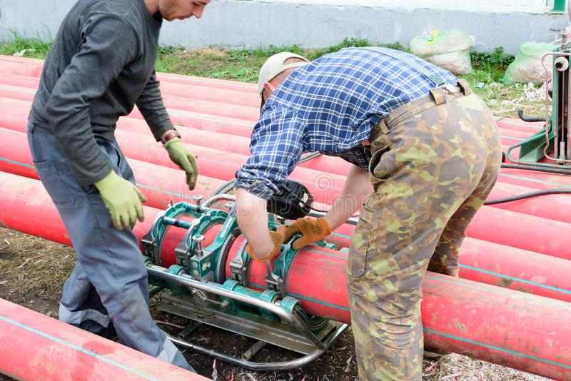 The specialist installs a welding machine for welding of plastic pipes. Polyethylene pipes for electric cables royalty free stock image
