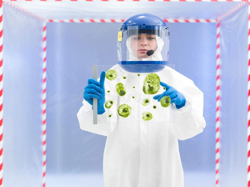 Specialist in protective suit holding biological sample. Person in protective suit holding microorganism samples on a glass slide and pointing to one of them in royalty free stock image