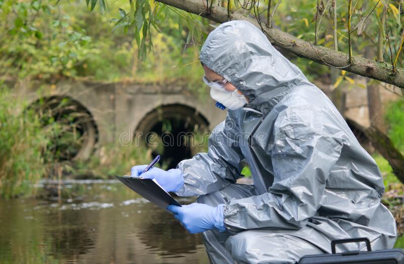 Specialist, in a protective suit, mask and gloves, working with toxic substances, records the results of a sample of liquid from royalty free stock photos