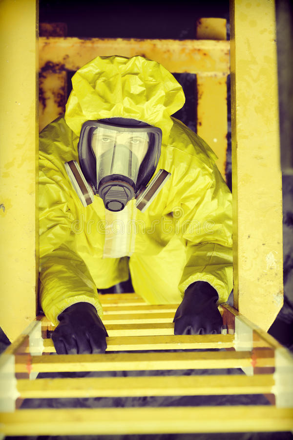 Specialist in protective suit and mask on ladder. Overhead view of specialist in protective suit and mask on ladder royalty free stock photos