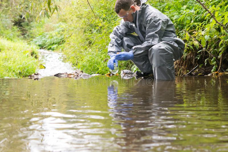 A specialist in a protective suit takes water into a flask from a river for analysis after the release of chemical agents from the. A specialist in a protective royalty free stock photos