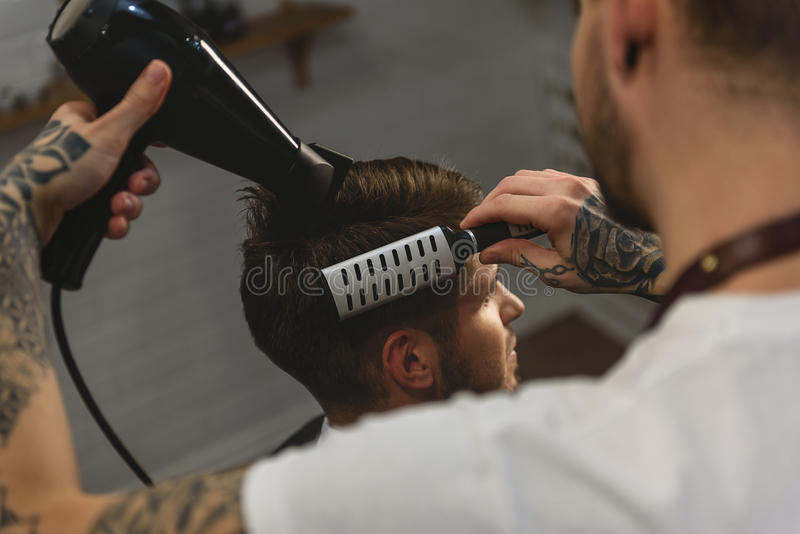 Specialist som använder den hårtorken och hårkammen royaltyfri fotografi