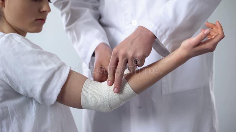 Specialist som tar omsorg av den sårade armbågen som förbinder, första hjälpen i traumaklinik royaltyfri foto