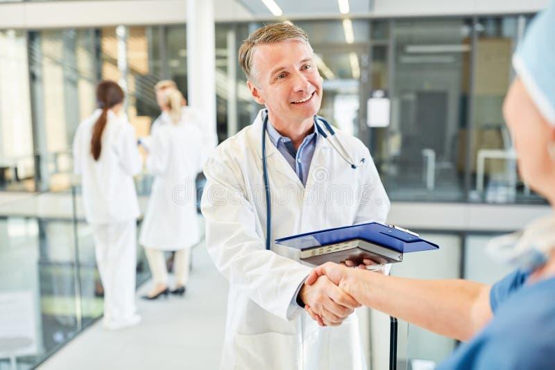 Specialista che stringe le mani con un chirurgo fotografia stock