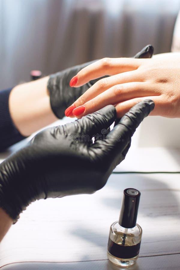 Specialista del manicure nelle cure nere dei guanti circa le unghie delle mani Il manicure dipinge le unghie con smalto rosso Sal immagini stock libere da diritti
