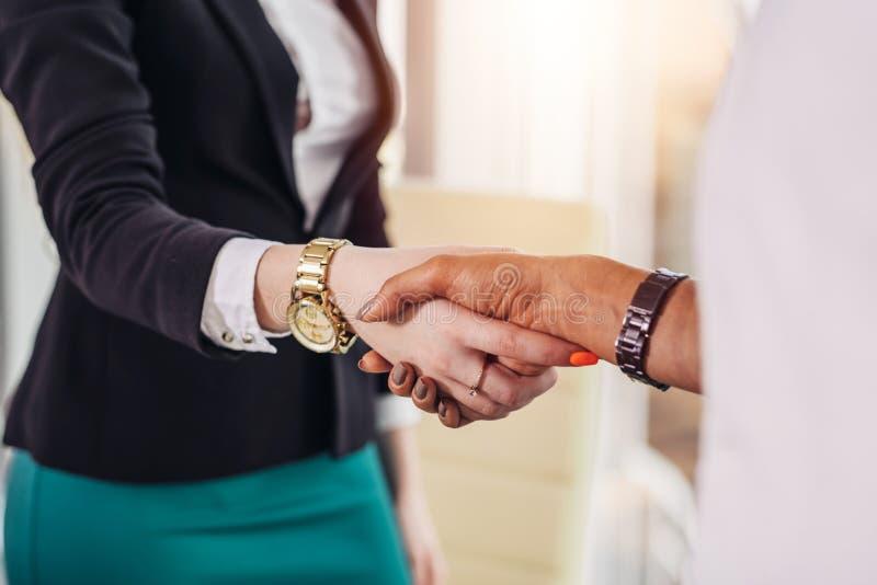 Specialista femminile che stringe le mani con una donna dopo il riuscito lavoro che se la congratula fotografia stock