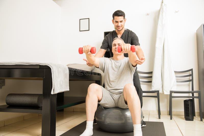 Specialista Helping Man Sitting sulla palla di esercizio e sollevare muto fotografia stock libera da diritti
