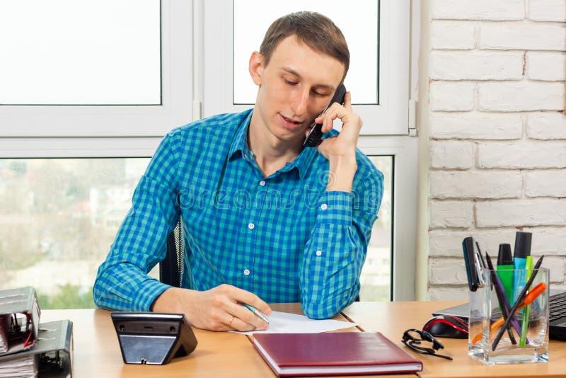 Specialista nell'ufficio che parla sul telefono in preparazione delle informazioni di registrazione fotografia stock