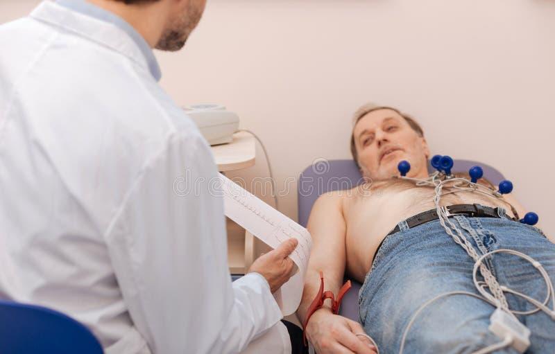 Specialista prominente che legge i risultati dell'ecocardiogramma fotografia stock