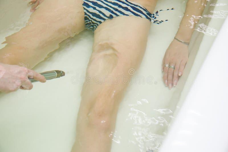 Specialisten applynig watergeneeskunde in bad Onderwaterhydromassage in schoonheidssalon royalty-vrije stock foto's