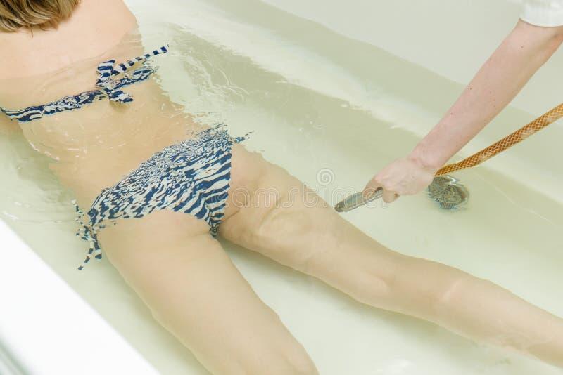 Specialisten applynig watergeneeskunde in bad Onderwaterhydromassage in schoonheidssalon stock afbeelding