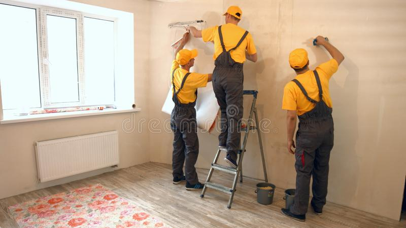 Specialists wallpapering in the house. Contractor workers preparing wall for wallpaper decoration. Brigade of builders making apartment renovation stock photo