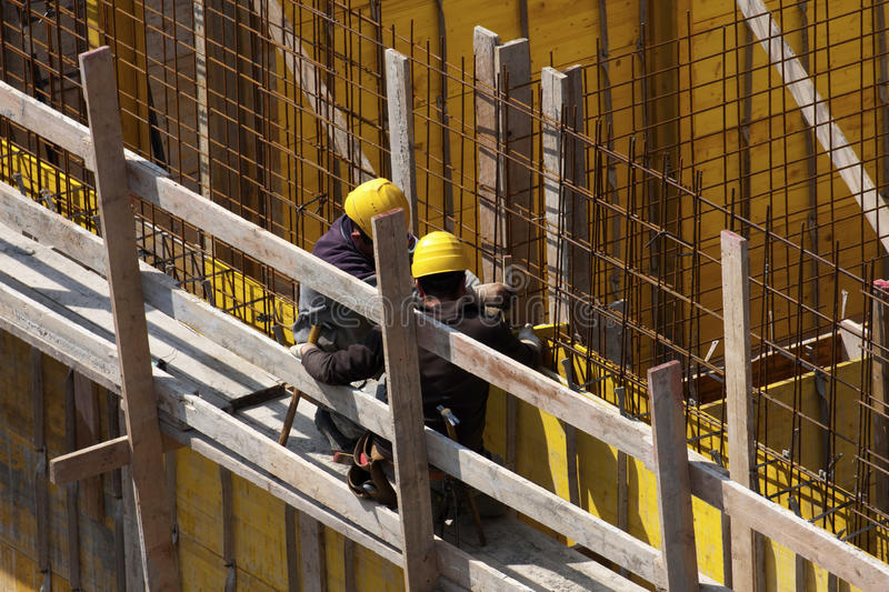 Specialists at work on construction site in reinforcing frame stock image