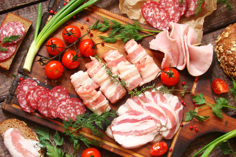 Specialità gastronomiche, carne affumicata, bacon, verdure, pomodori, verdi immagini stock libere da diritti