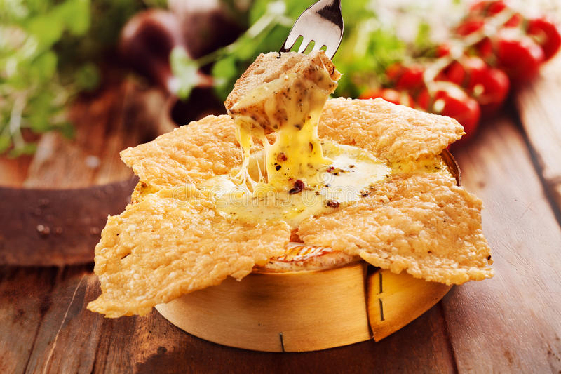 Speciality grilled, fried or roast camembert oven cheese dip. Person dipping a toasted crouton into a speciality grilled, fried or roast camembert oven cheese royalty free stock photo
