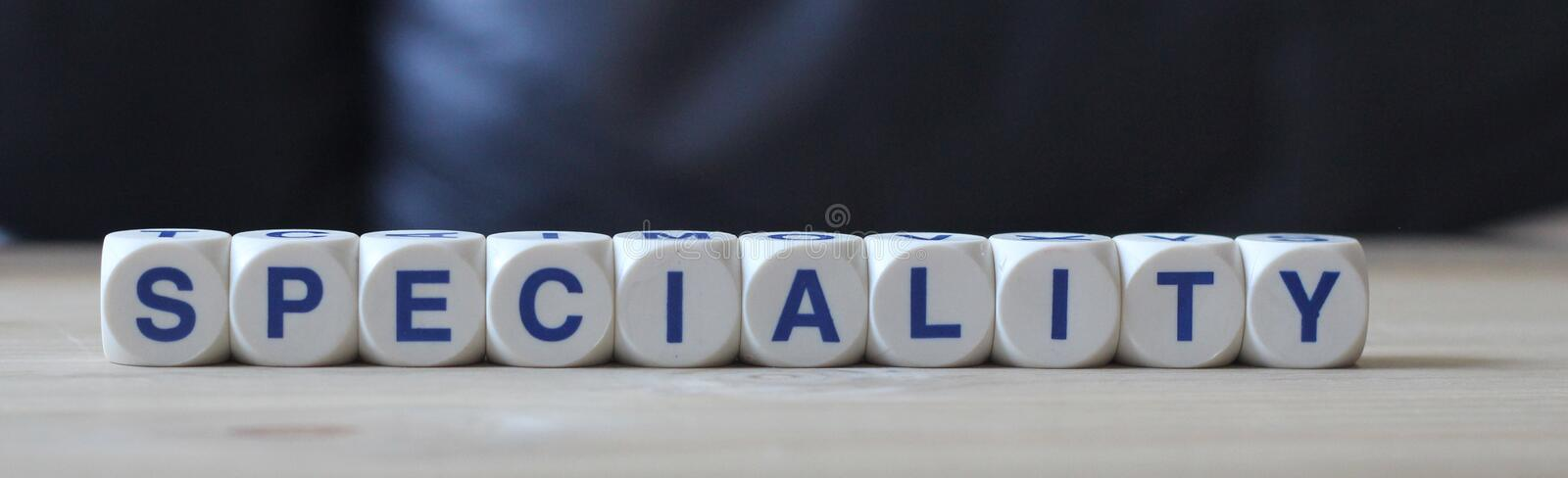 Speciality. Letters cube wordings on wood table royalty free stock photos