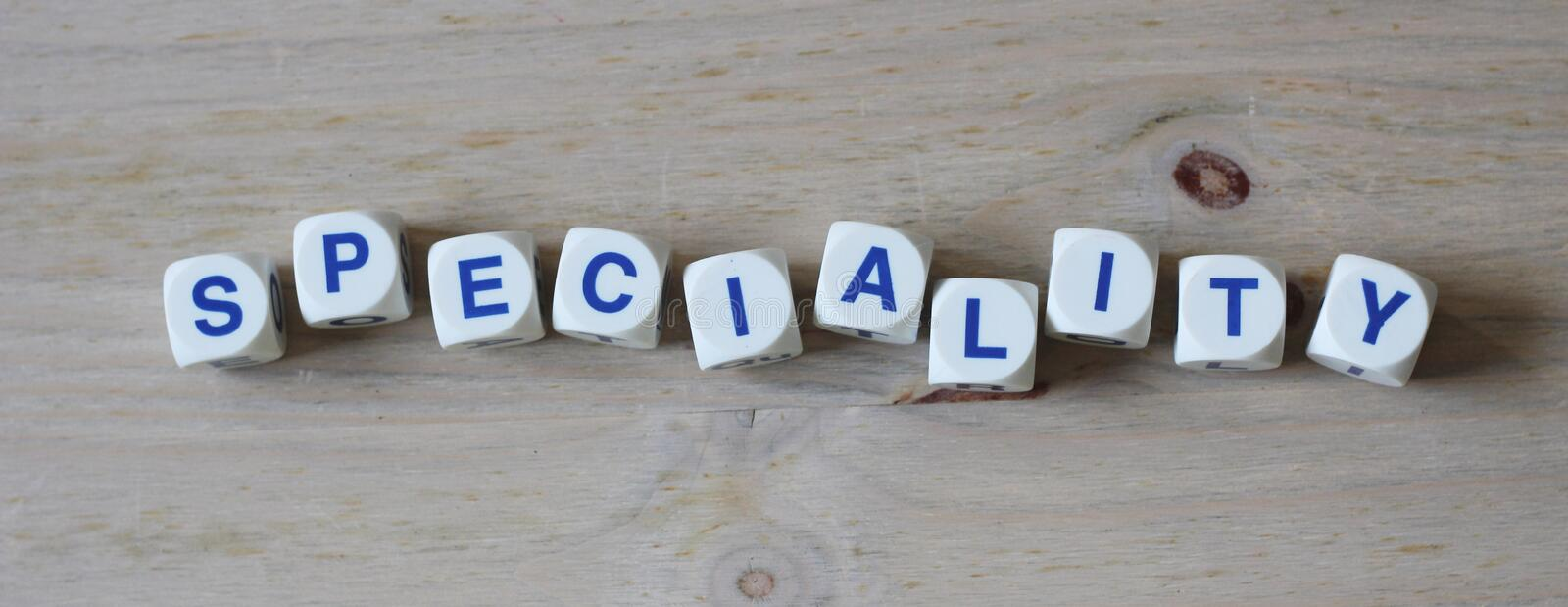 Speciality. Letters cube wordings on wood table stock photo