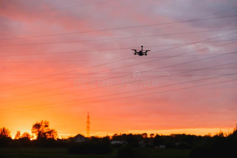 Specialtillverkat surrflyg på solnedgång nära kraftledningar fotografering för bildbyråer