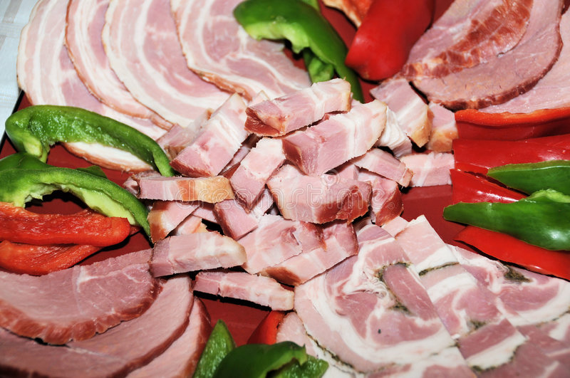 Specialty meats. With green and red peppers royalty free stock photos