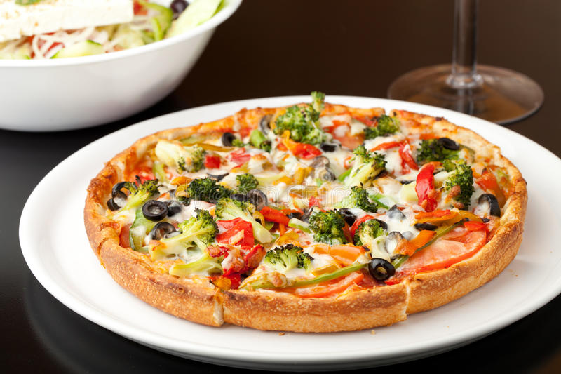 Specialty Pizza Toppings. A fresh medium size specialty pizza with extra toppings hot and fresh out of the oven. Shallow depth of field royalty free stock image