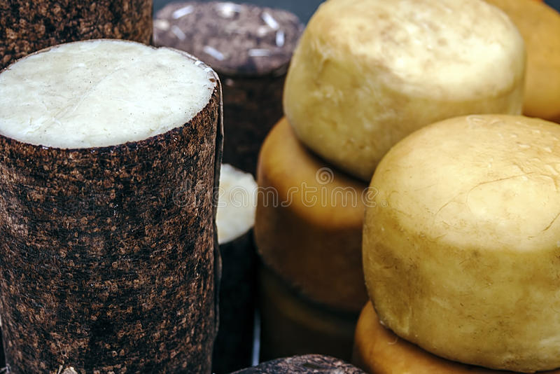 Specific cheese for Romania 2. Cheese wrapped in fir bark and wheels of smoked cheese. Specific area Brasov, Romania royalty free stock photos