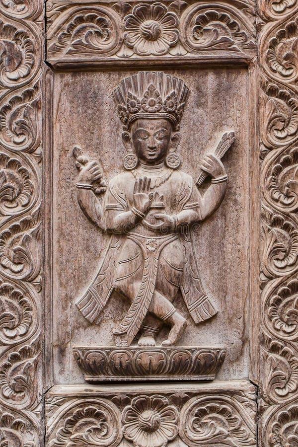 Specificera den träsned dörren i den hinduiska templet, Katmandu, Nepal bakgrund close upp arkivbild