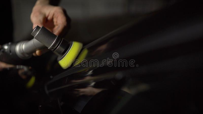 Specificera f?r bil - h?nder med orbitalpolisheren i auto reparation shoppar Selektivt fokusera Bilpolering och LCP-korrigering royaltyfri foto