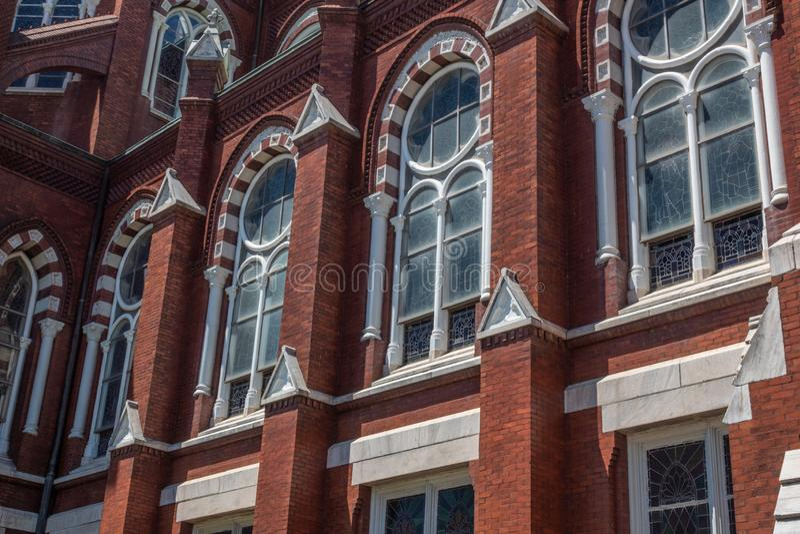 Specificera yttre arkitektur av den gotiska nypremiärkyrkan för röd tegelsten med välvda fönster royaltyfri bild