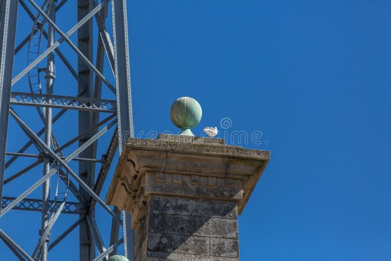 Specificerad sikt på granitpelaren med sfären överst, D Luis brostruktur och blå himmel som bakgrund royaltyfri foto