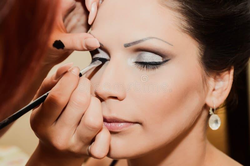 Specificerar makeup på brud close upp arkivfoton