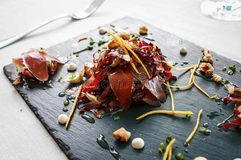 Speck smoked ham appetizer in Cortina D`Ampezzo, Dolomites, It royalty free stock photo