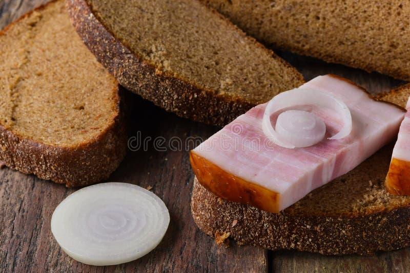 Speck auf einer Scheibe des Roggenbrotes mit einem Ring der Zwiebel auf einem Holztisch lizenzfreies stockfoto