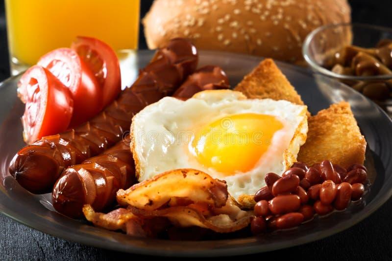 Speck, gegrillte Würste, Spiegelei, Bohnen, Bohnen, Toast, Tomaten, frischer Saft der Pilze - volles englisches Frühstück stockfoto