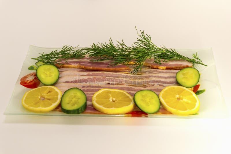 Speck geschnitten in dünne Scheiben mit Dill und Gurke und mit Zitrone lizenzfreies stockbild