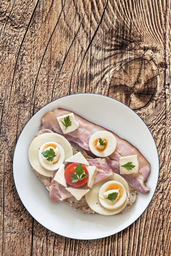 Speck-Käse-Ei-Schinken und Tomaten-Sandwich auf hölzernem Hintergrund lizenzfreie stockbilder