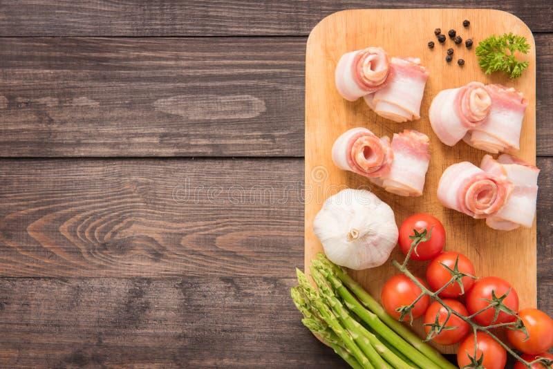 Speck rollt mit Tomate, Knoblauch, Spargel auf hölzernem Hintergrund stockfotografie