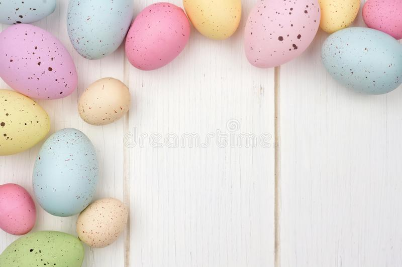 Speckled Easter egg corner border against white wood. Pastel speckled Easter egg corner border against a white wood background royalty free stock photography