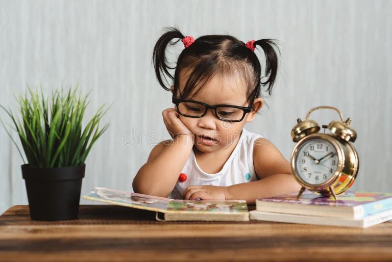 Spectacle de port semblant sérieux mignon de petit enfant en bas âge asiatique lisant un livre sur une table photographie stock