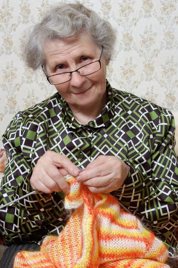 Spectacled Großmutter bindet Wolljacke stockfotografie