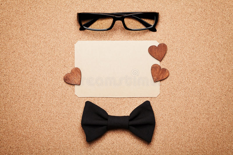 Spectacles, bowtie and empty paper blank in Happy Fathers Day, cork board background, top view, flat lay stock photos