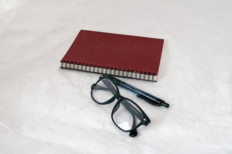 Spectacles and the pen and dark red note book and the black ring of spine book. royalty free stock photos