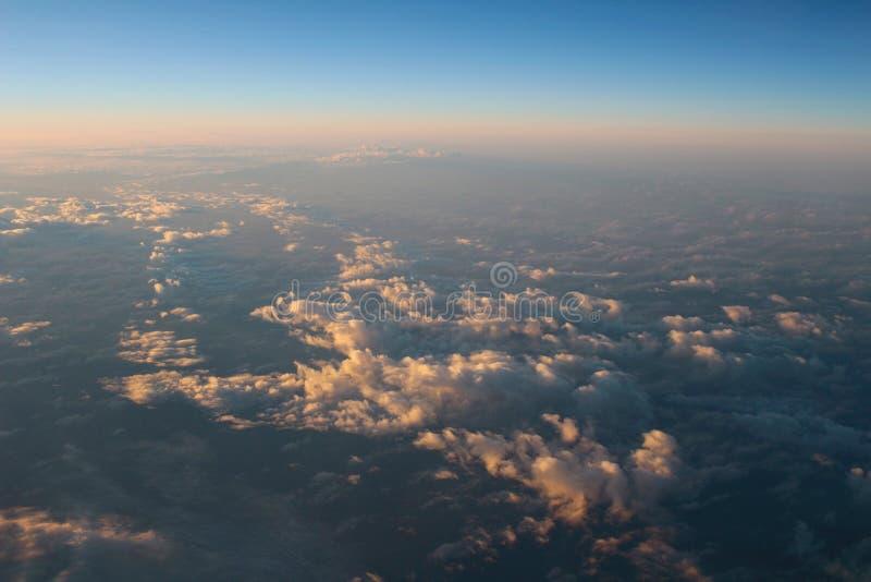 Spectaculaire mening van een zonsondergang boven de wolken van vliegtuigwind royalty-vrije stock afbeelding