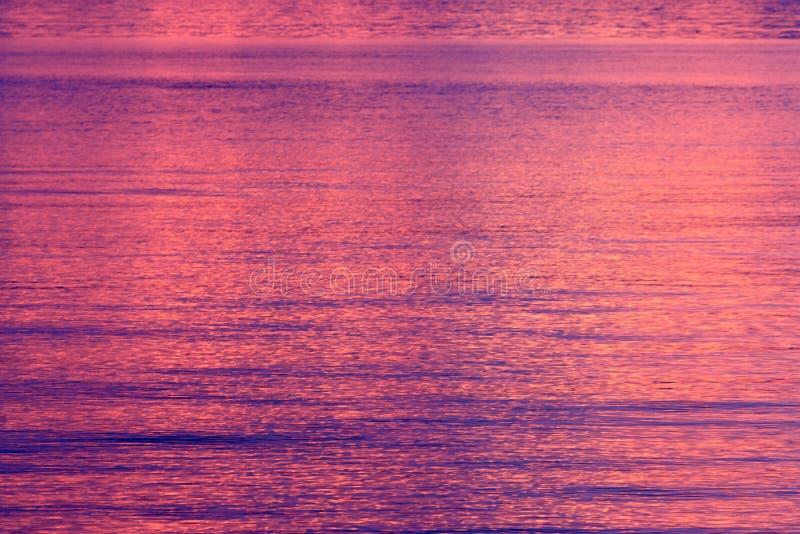 Spectaculaire roze die zonsondergang water wordt overdacht stock afbeeldingen